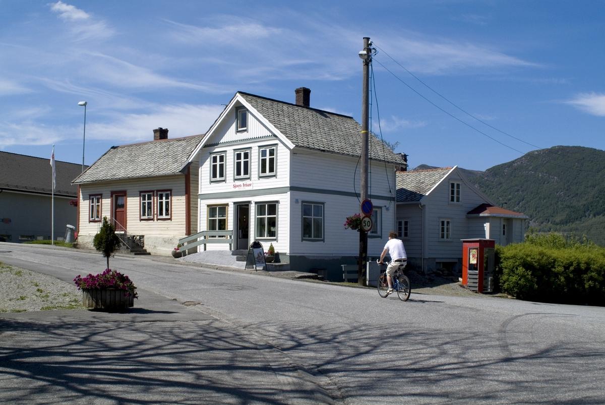 Telefonkiosken står ved Ølen kai, og er en av de 100 vernede telefonkioskene i Norge. De røde telefonkioskene ble laget av hovedverkstedet til Telenor (Telegrafverket, Televerket).  Målene er så å si uforandret.  Vi har dessverre ikke hatt kapasitet til å gjøre grundige mål av hver enkelt kiosk som er vernet.  Blant annet er vekten og høyden på døra endret fra tegningene til hovedverkstedet fra 1933. Målene fra 1933 var: Høyde 2500 mm + sokkel på ca 70 mm Grunnflate 1000x1000 mm. Vekt 850 kg. Mange av oss har minner knyttet til den lille røde bygningen. Historien om telefonkiosken er på mange måter historien om oss.  Derfor ble 100 av de røde telefonkioskene rundt om i landet vernet i 1997. Dette er en av dem.