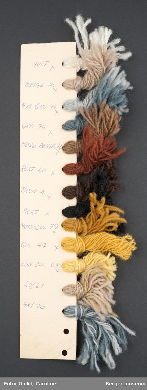Pappremse med hull på hvers side, der garnprøver i forskjellige farger er knytet på. Garnfargene er nummerert med blå kulepenn på kartongen.