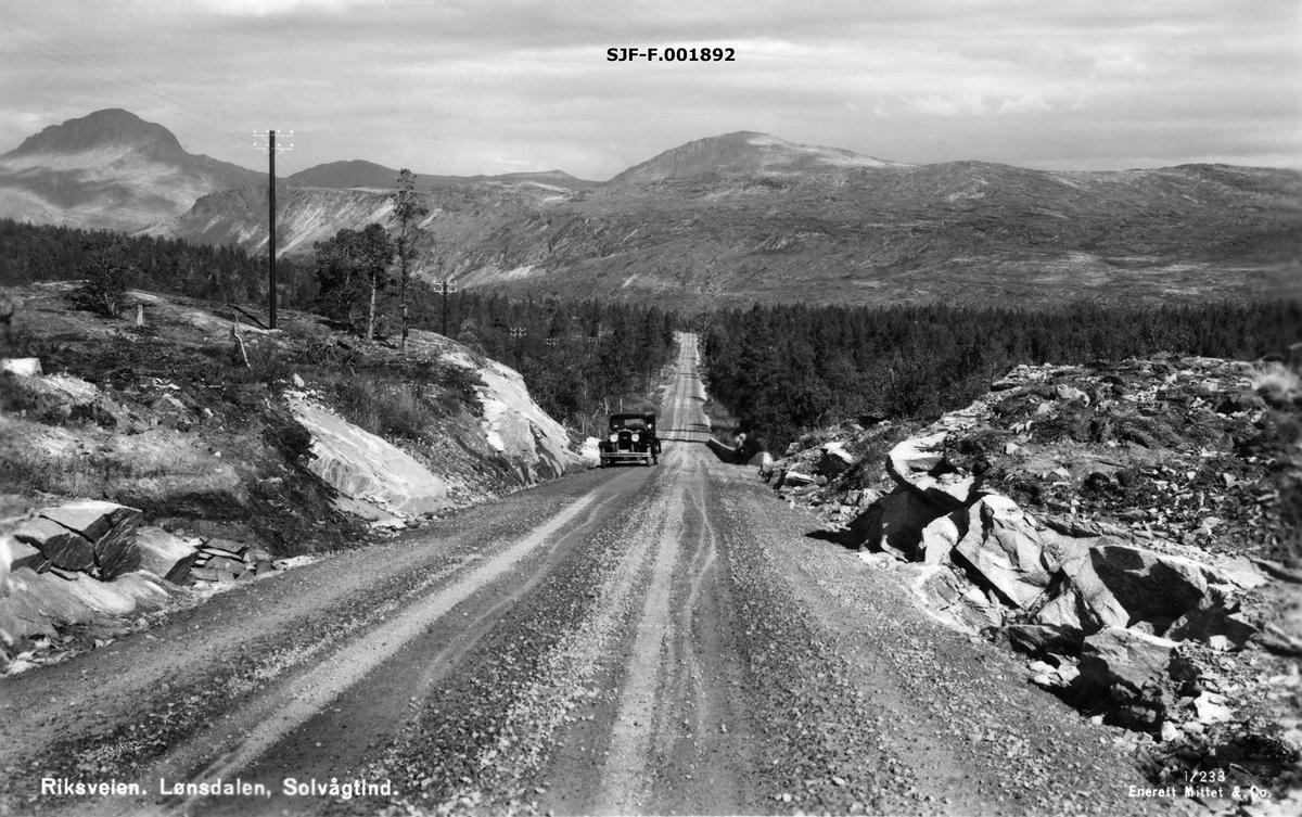 Riksvegen gjennom Lønsdalen (Luonosvagge) i Saltdal kommune i Nordland, slik den så ut i 1930-åra.  Fotografen har stått på et sted hvor vegen går i ei lav skjæring over et lite bergparti.  En bil er på veg opp mot opptaksstedet.  I bakgrunnen en forholdvis lang rett strekning gjennom glissen skog.  Over skogen troner en fjellrygg, muligens Tjørnfjellet (Girnno).  Helt til venstre rager Solvågtind mot himmelen.