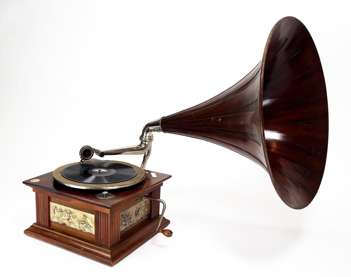 Grammofon med sveiv som er utført med treverk i overflate på lyddåse og i trakta. Tre av sidene har dekorfelt som bl.a. forestiller krigere fra antikken eller romertida. Sveiva har håndtak av tre. Den svingbare armen med stift er i sin helhet av metall. Overflaten der plata skal ligge er av filt.