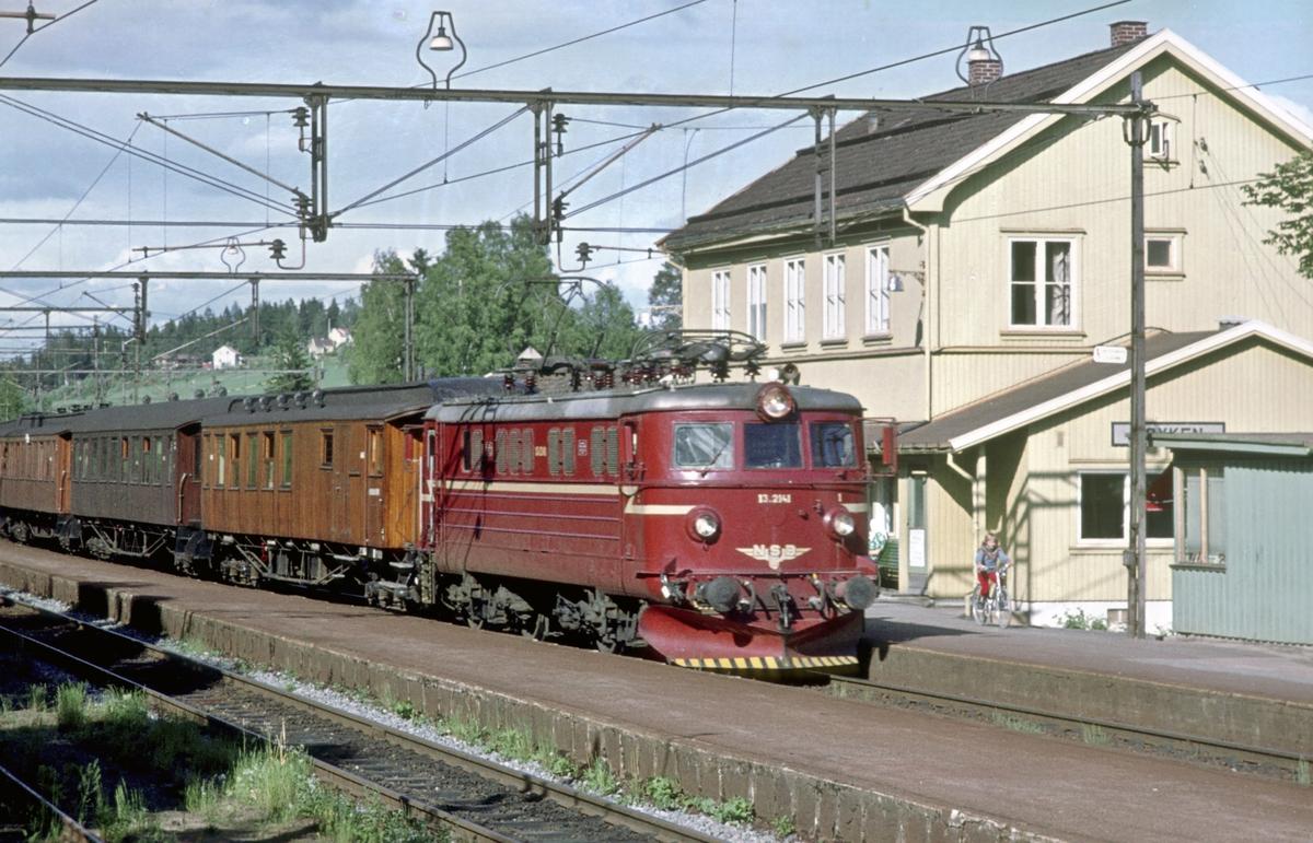 Persontog Oslo V - Spikkestad med elektrisk lokomotiv El 13 2141 kjører inn på Røyken stasjon. Mens de fleste togene var motorvognsett som pendlet mellom Asker og Spikkestad ble det kjørt noen rushtidstog hele veien til/fra Oslo V.