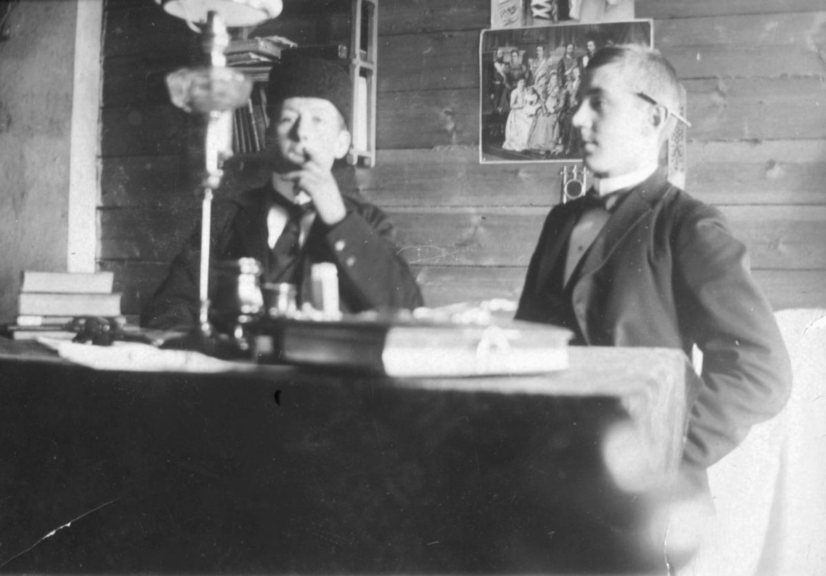 Dette bildet er trolig tatt på begynnelsen av 1900-tallet. To unge menn sitter ved et bord. De er kledd i jakker og vester. Mannen til venstre har på seg slips og lue. Han ser ut til å røyke. Mannen til høyre har en penn eller noe lignende bak øret og en sløyfe rundt halsen. På bordet kan man se bøker, papir og en lampe. På veggen bak kan man se fotografier av kvinner og en bokhylle.