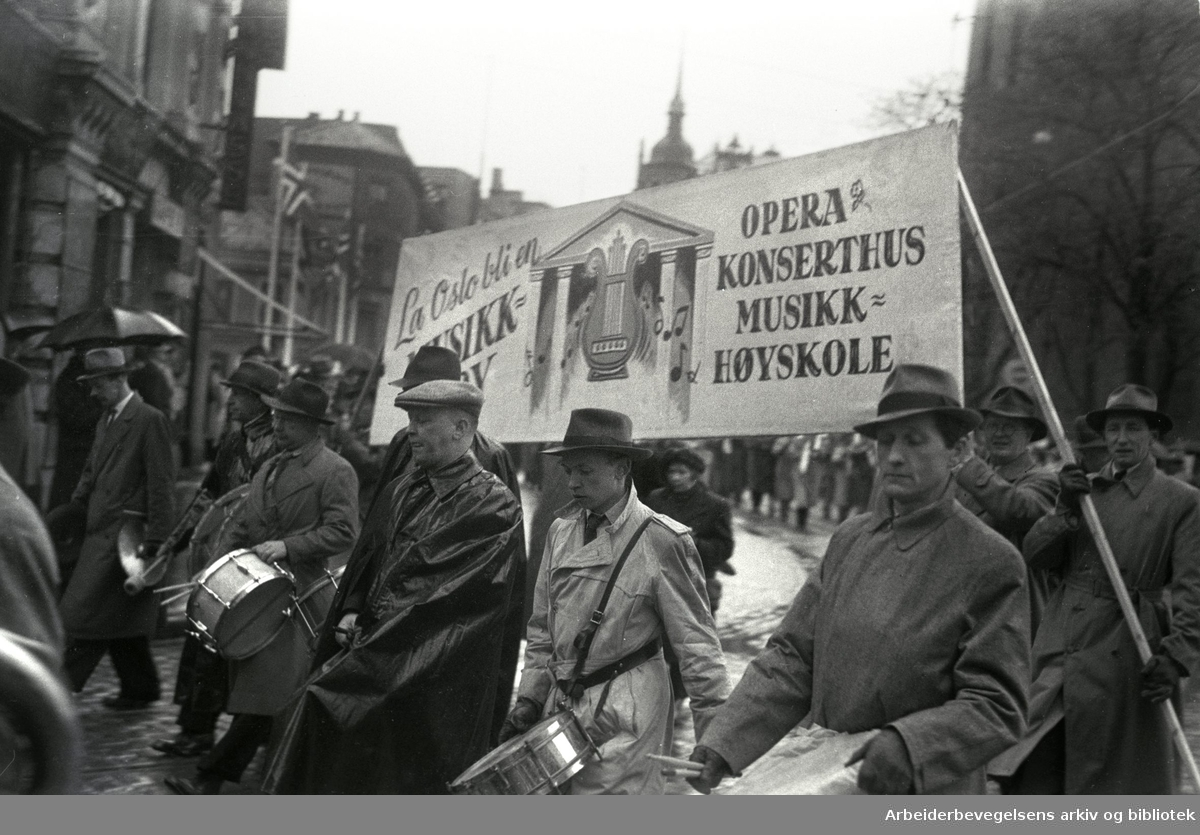 1. mai 1948, demonstrasjonstoget. Parole: La Oslo bli en musikkby. Opera Konserthus Musikkhøyskole.