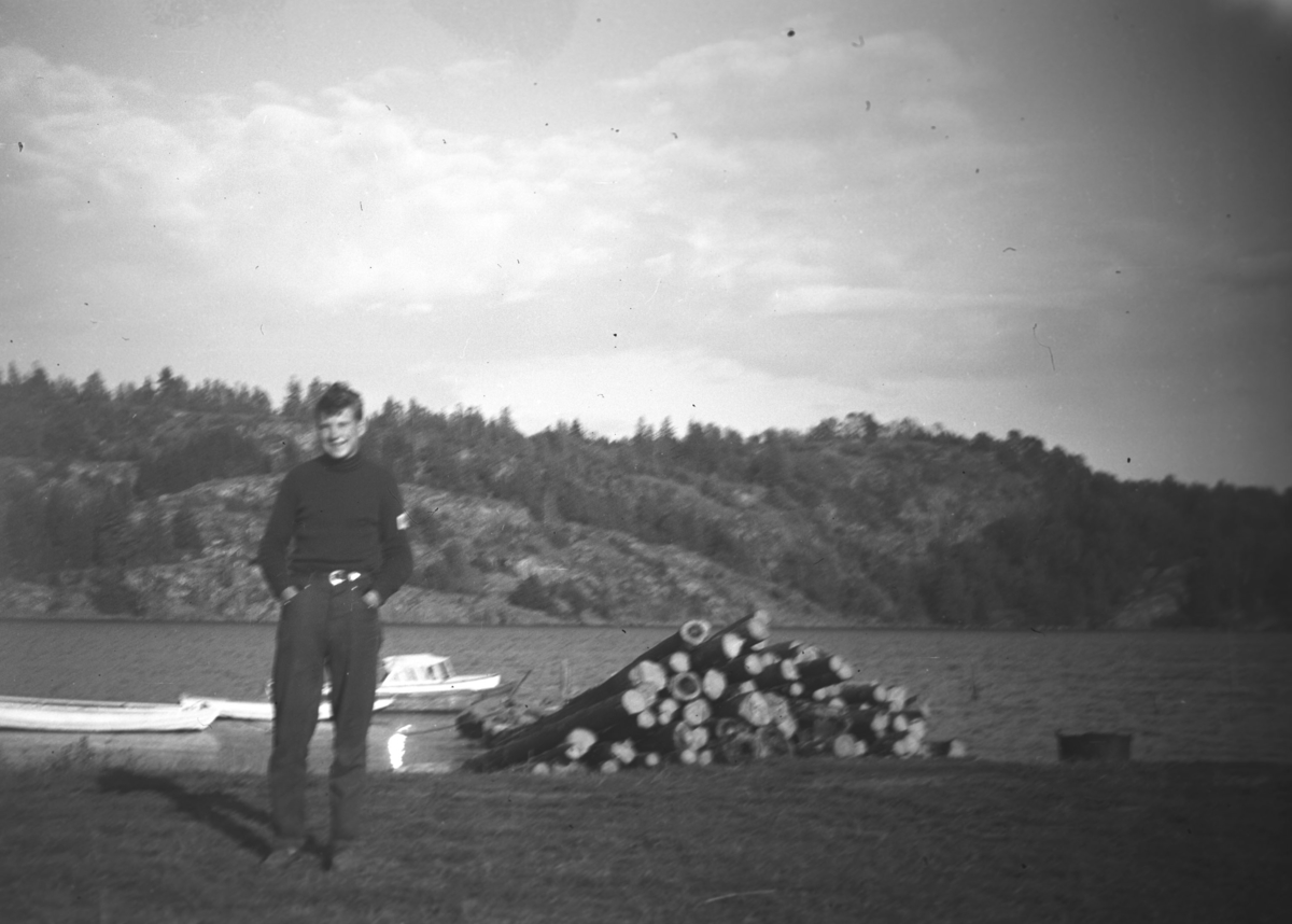 En ukjent gutt iført mørke klær, fotografert ved bredden av en innsjø eller havet. Stedet er ukjent.
