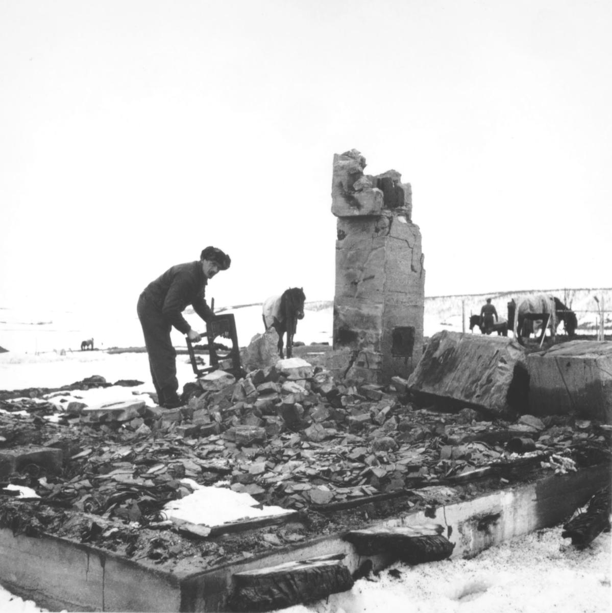 En branntomt, trolig i Porsanger eller Karasjok. Det er kun grunnmuren og litt av pipa igjen. En mann leiter i ruinene. Det er noen hester med på bildet.
