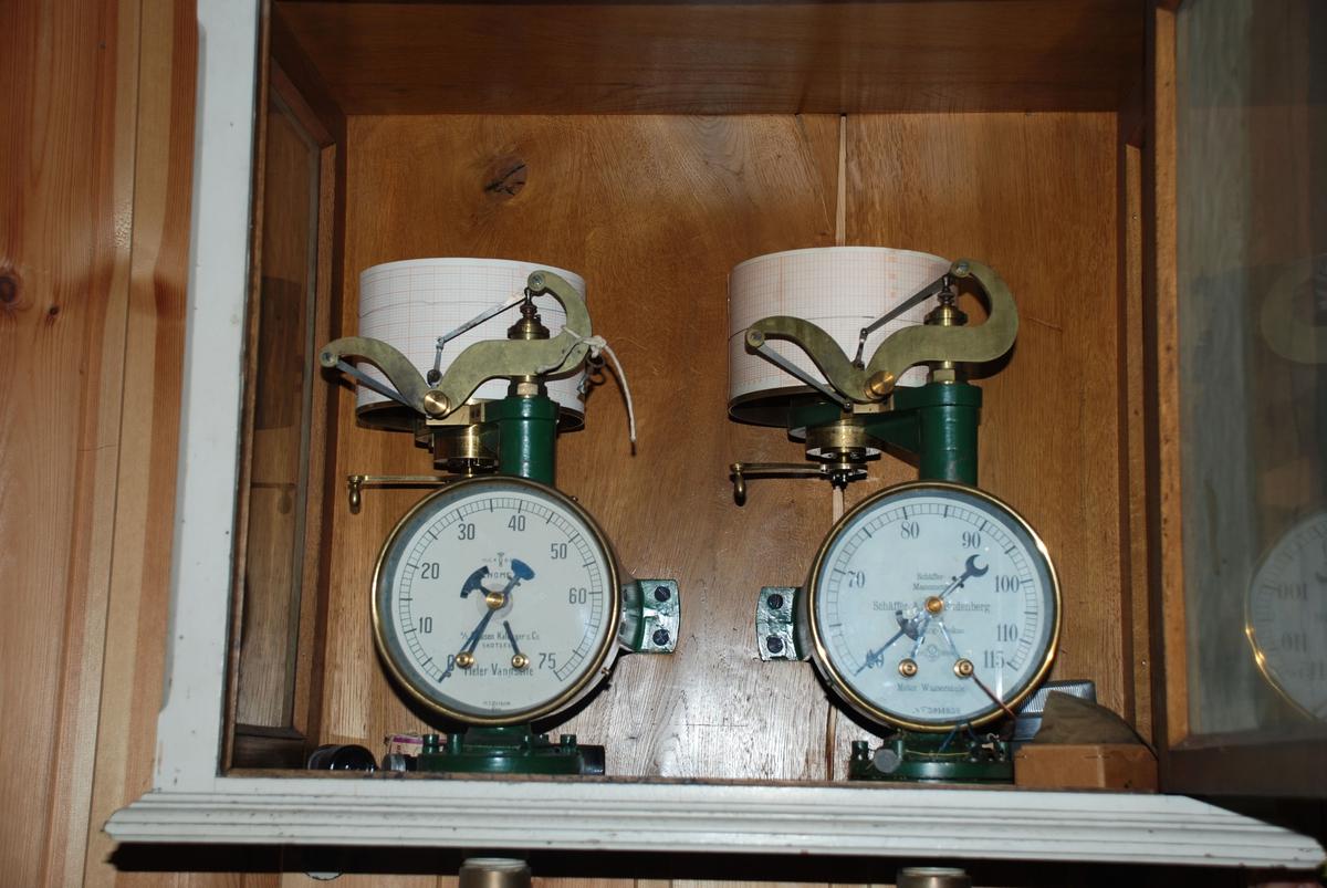 Vegghengt rektangulært skap med glassdør. Inneholder 2 manometre for måling av vanntrykk. Papirrull på toppen der målingene automatisk registreres som graf. Manometrene står i bunnen av skapet og er festet i bakveggen.