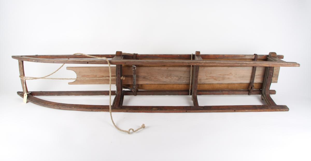 Fiskekjelke i tre med midtplanke og sittepute, for to personer. Forsterket med bolter  i tre, ved første og tredje meiefeste. Forseggjort pute med tre remfester under puten.