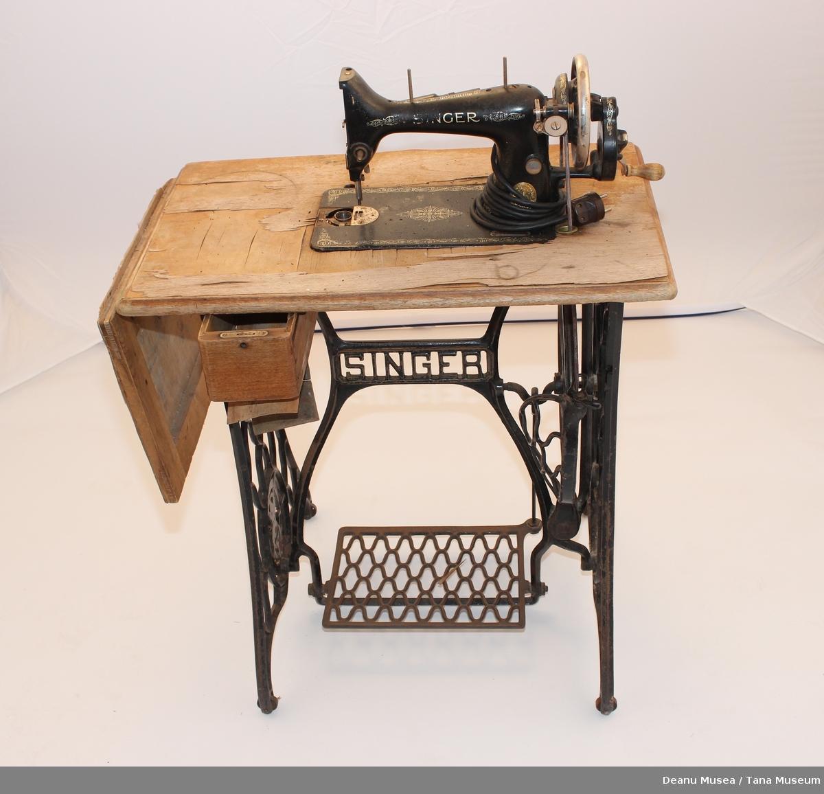 Tråsymaskin med sybord. Lampe med lampettledning montert på symaskinen. En skuff i front. Kan folde ut sybordet.