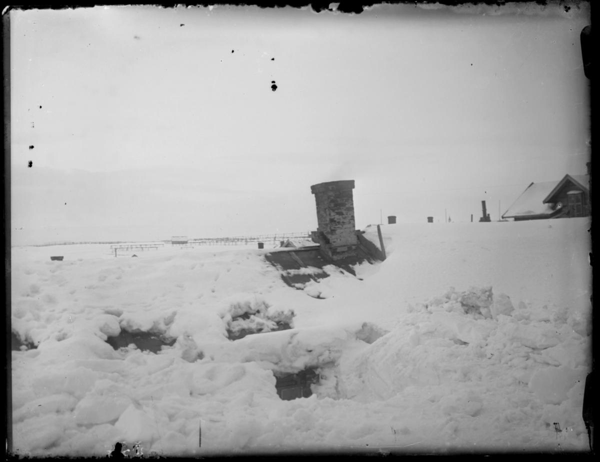 Snøvinter i Vardø. I forgrunnen av bildet en liten bygning som er helt nedsnødd. Bare en skorstein stikker opp av snøen