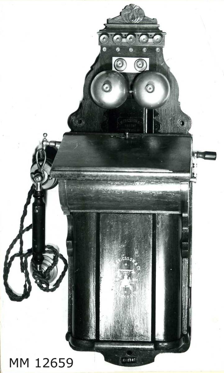 """Väggtelefon m/1895. Se även foto på MM 8252. Apparaten är innesluten i en kåpa av mahogny. Klyka för handmikrotelefonen placerad  på vänster sida av apparaten. Märkning överst: """"L.M. Ericsson & Co Patent Stockholm. På batterilocket: Firmamärke som utgöres av en bild föreställande en bordstelefon samt texten: Trade Mark. Kring bilden: L.M. Ericsson & Co Stockholm. Märkning innanför locket: 719491. Handmikrotelefonen märkt: Made in Sweden by AB L.M. Eriksson & Co Stockholm Patented oct. 29 1895. (Firmans namn ombildades år 1896 till Allmänna Telefon AB L.M. Ericsson)."""