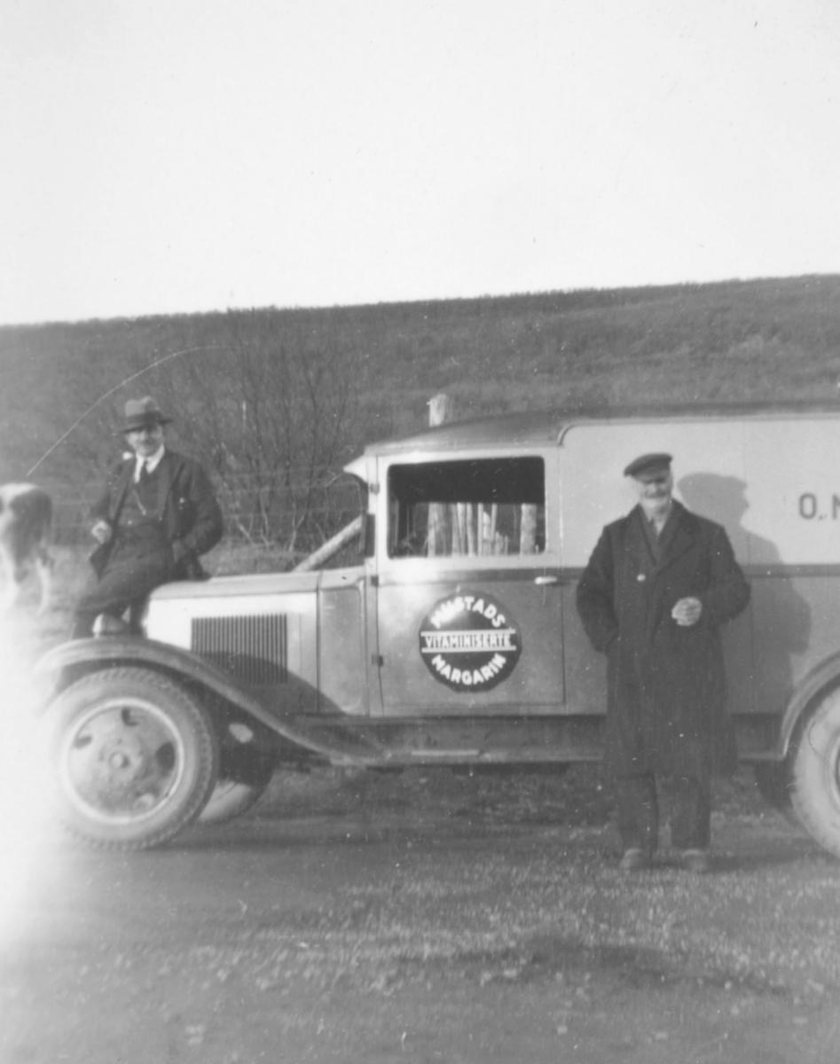 To menn ved siden av en bil som kan være en Chevrolet varevogn, 1930-33 mod. En står ved siden av bilen, og den andre sitter på panseret. Det er et stort rundt merke på døra til bilen. Det står Mustad margarin.