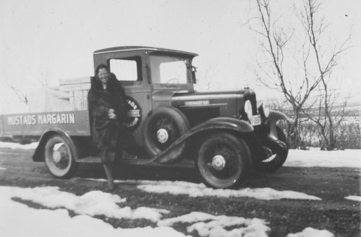 En dame står ved siden av en Chevrolet pickup 1931-33 modell. På lastekarmen står det Mustads margarin. Det er litt snø på bakken. I veikanten et par trær eller busker.