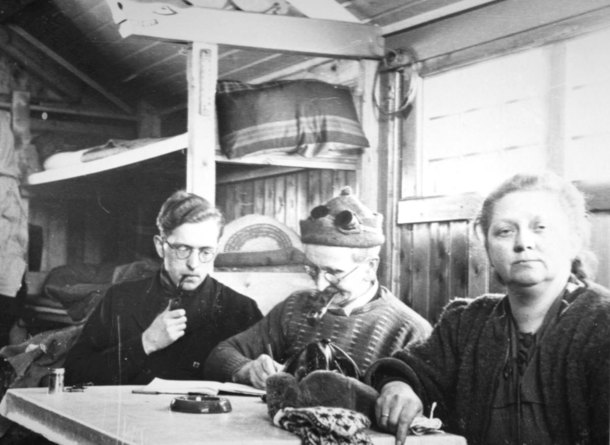 To menn og en dame sitter ved et bord inne i en hytte. Til venstre er det køysenger, og til høyre et lite vindu. På bordet ligger det en skinnlue og et par selbuvanter. Mennene røyker pipe. Den ene skriver i en bok. Begge mennene har briller på.
