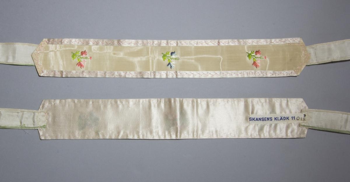 Strumpeband för dam, ett par. Troligen tillverkat av ett mönstervävt tyg med tre blommor. Baksidan täckt med ett rosa sidenband vars kanter på långsidan är vikt framåt och nersydda med kråkspark. Kortsidorna är vinklade i en trubbig spets. Knytband tillverkade av ett sidentyg, vars långsidor är fållade på maskin. Knytbanden är fastsydda för hand på kortsidorna.