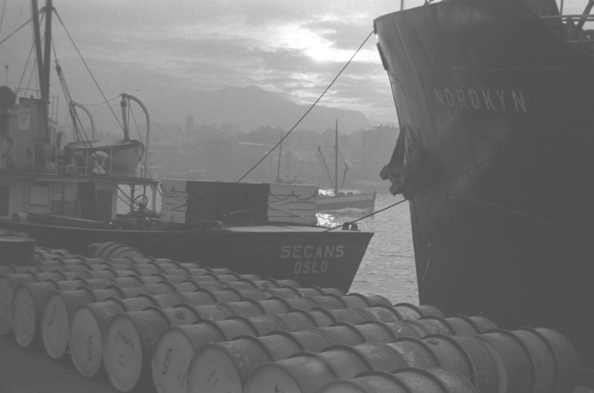 Flere større båter ligger fortøyd til en kai med masse tønner oppå. Stedet er ukjent.