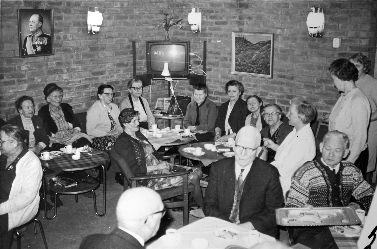 Eldre kvinner og menn drikker kaffe på Soldathjemmet. Til venstre sitter veterinær Louise Iversen, i kvit bluse.