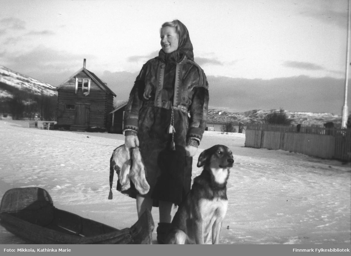 Herlaug Mikkola i pesk, klar til tur. I forkant en pulk, og en hund sitter og venter på å bli med på tur. I bakgrunnen ser vi melkebua på gården