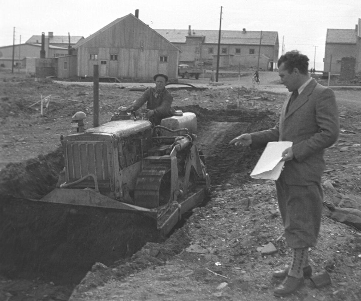 En bulldoser er begynt å grave ut tomta til Vårbrudd i Vadsø. Mannen som står med noen papirer i hånda er Alfred Bjørkli. Føreren av maskinen er ukjent.