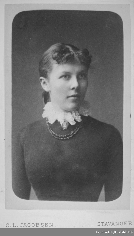 Portrett av en kvinne iført er mørk, tynn genser. Hun har en blondekrage rundt halsen og et kjede henger nedenfor kragen. Portrettet er tatt hos C.L. Jacobsen atelier i Stavanger.