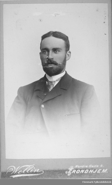 Portrett av en mann med helskjegg. Han har en mørk dressjakke på seg med hvit skjorte og et stripet slips under.