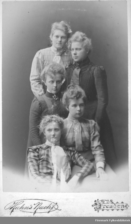 Gruppeportrett av fem kvinner. De har kjoler i forskjellige form, farger og mønster. Damen nederst på bildet har et halstørkle og hun i midten på bildet har en brosje i halsen.