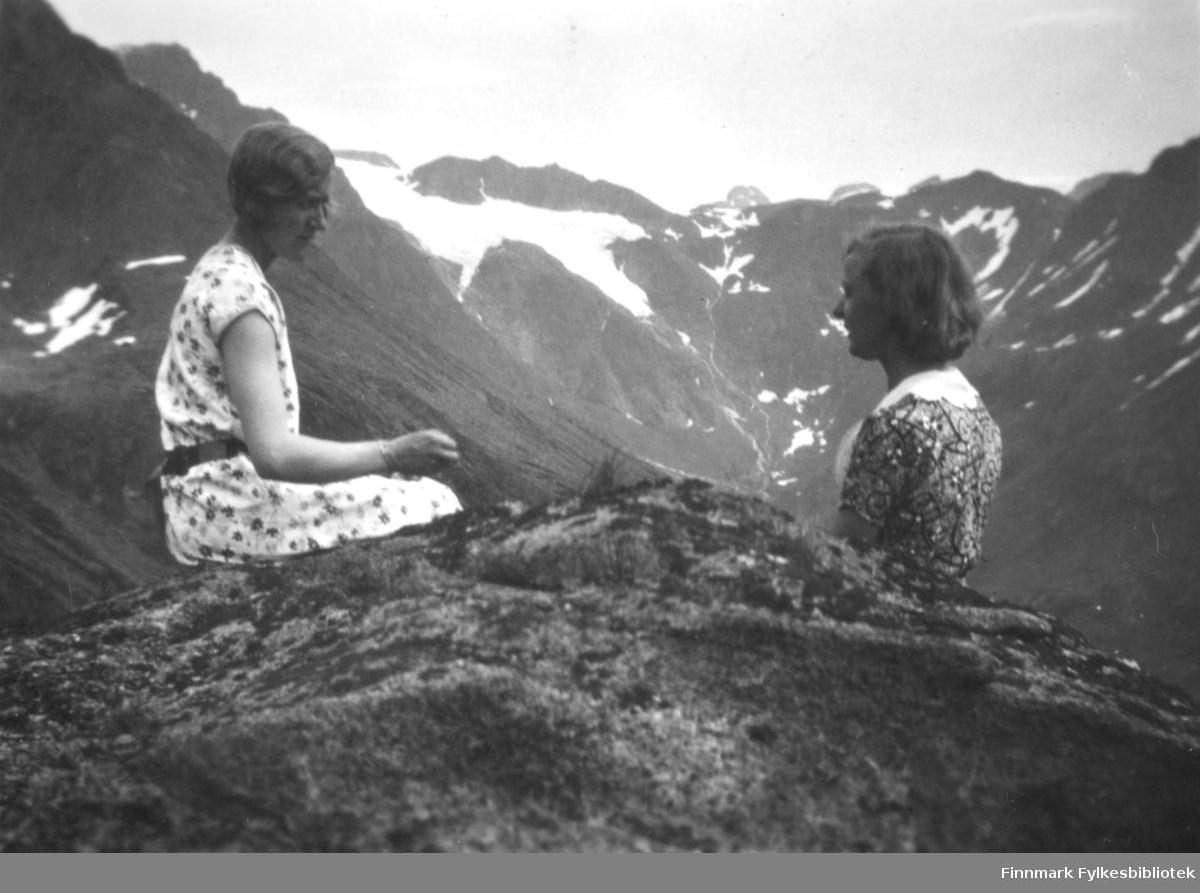 To damer sitter på en fjelltopp. Hun til venstre har en kortermet mønstret kjole med sort belte. Hun til høyre har en mørk kjole med mønster og hvit krave. Det er stein og litt lyng/gress på toppen rett bak dem. I bakgrunnen er flere høye fjell med is-/snøflekker på toppene. En større is-/snøflekk midt på bildet er muligens deler av Øksfjordjøkelen.