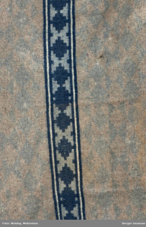 En prøve i hel bredde. Teppe med gjentagende mønster som blir brutt av samme mønsterbord i en annen farge.