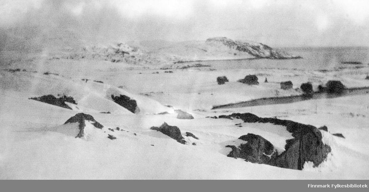 Hasvik en vinterdag. Det er en del snø i terrenget med noen store steiner stikkende opp her og der. Noen bygninger står ved den nærmste vika/fjorden. Ved fjorden lengst borte ses såvidt noen bygninger. En holme ligger ytterst i fjorden. Noen tunge skyer på himmelen, men det er ganske stille på sjøen.