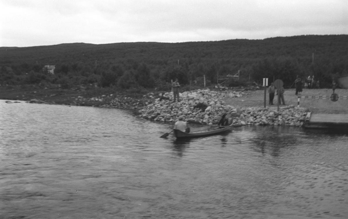 To personer sitter i en elvebåt og flere står på land. Stedet er ukjent, men kan være Tanaelva ved Utsjoki i Finland.