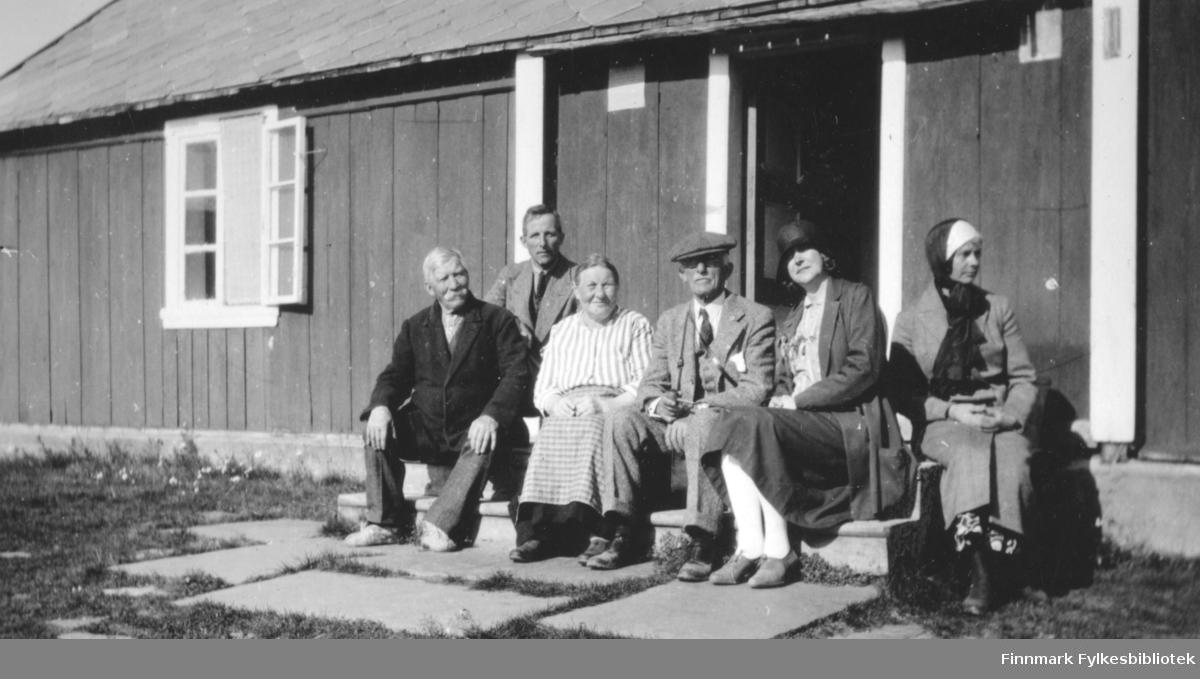 Seks mennesker på trappa til en bygning, sannsynligvis stallen/fjøset til herregården Saga. Mannen til venstre har penklær med en mørk frakk. Til høyre for han sitter en mann med lysere jakke og en dame med rutete skjørt og stipete overdel. Den eldre herren i midten har ganske lys dress med hvit skjorte og slips og hatt på hodet. Damen til høyre for han har lyse bukser, mørkt skjørt, mørk jakke og et hodeplagg på seg. Damen helt til høyre har ensfarget drakt, en lue og et skjerf el. lignende rundt halsen/over hodet. Døra bak dem står åpen, samme med det todelte vinduet til venstre der ene delen står åpent. Bygget har skifertak og store steinheller foran trappa. Noe gress på bakken foran bygningen og sola skinner.