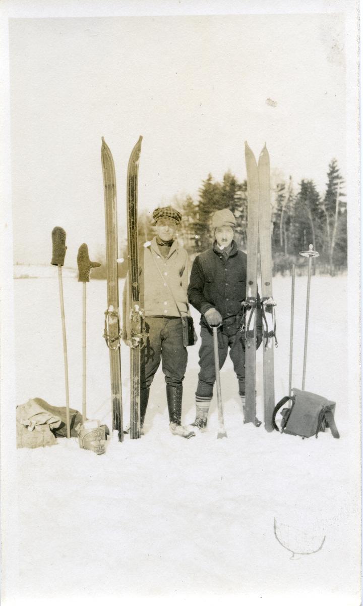 To menn oppstilt på isen. De har ski, staver og sekk ved siden av seg.