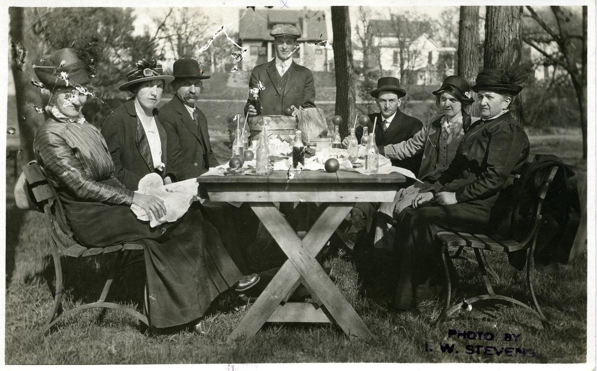 Tre menn og fire kvinner på picnic. De sitter ved et trebord under noen trær - med hus i bakgrunnen