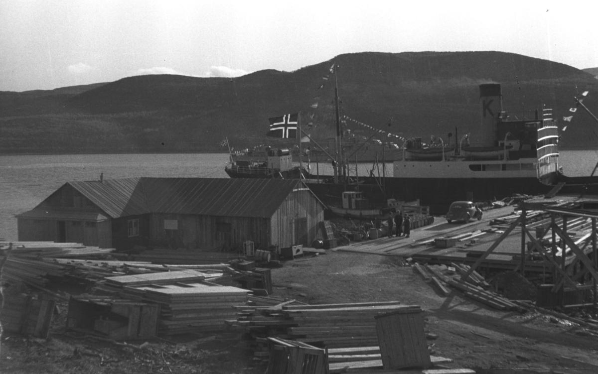 """Et stort skip ligger ved en kai. Skipet har flagg på hekken, fra masta og en """"k"""" malt på skorsteinen så bildet kan være tatt i forbindelse med Kong Haakons reise i Finnmark etter krigen. Stedet er ukjent."""