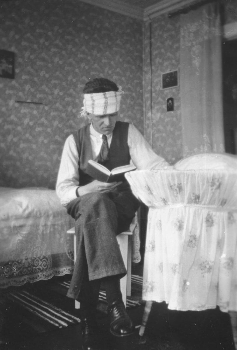 Tor Hauge beskriver dette bildet i en følgende måte: 'Min far Leif Hauge, med hodepine og barneskrik fra undertegnende'. Tor Hauge leser ei bok ved siden sengen til sønnen sin som sover