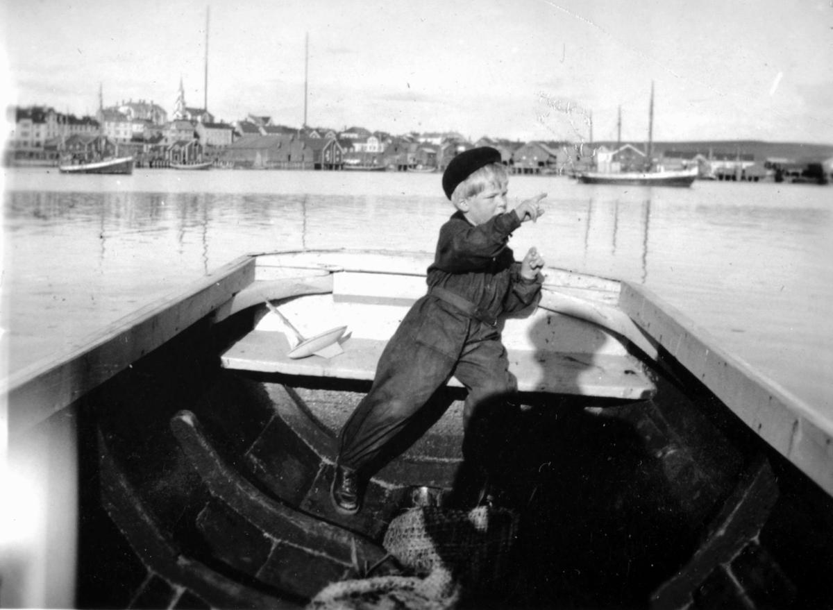 Tor Hauge som sitter i en åpen båt.  Sannsynelig skal han fram eller tilbake fra Vadsøya. I bakgrunnen ses en del av Vadsø by. Tor har en liten lekeseilbåt liggende ved siden av seg