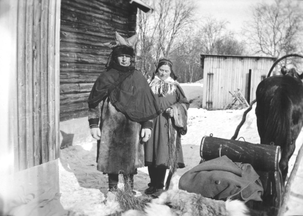 En mann og en kvinne kledt i samiske klær, står utenfor en trebygning. Ved siden av dem står en hest, spent foran en slede. I bakgrunnen er det et vedskjul. Bildet er antakelig tatt innover i Varangerfjorden, eller i Tana