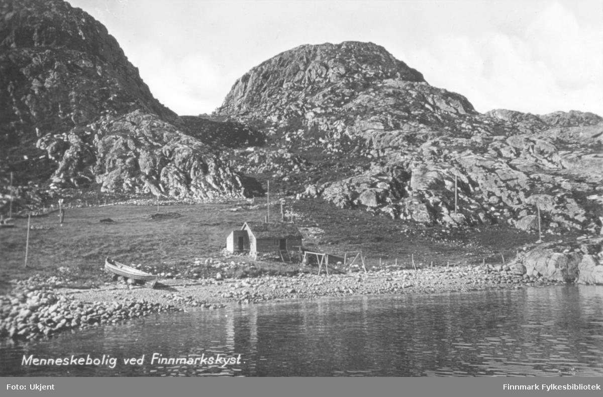'Menneskebolig ved Finnmarkskyst.' står det trykt på dette postkortet. På bildet kan man se et trebygg og en båt i fjæra. Bygget har et torvtak. Foran huset kan man se to trekonstruksjoner. I bakgrunnen kan man se fjell.