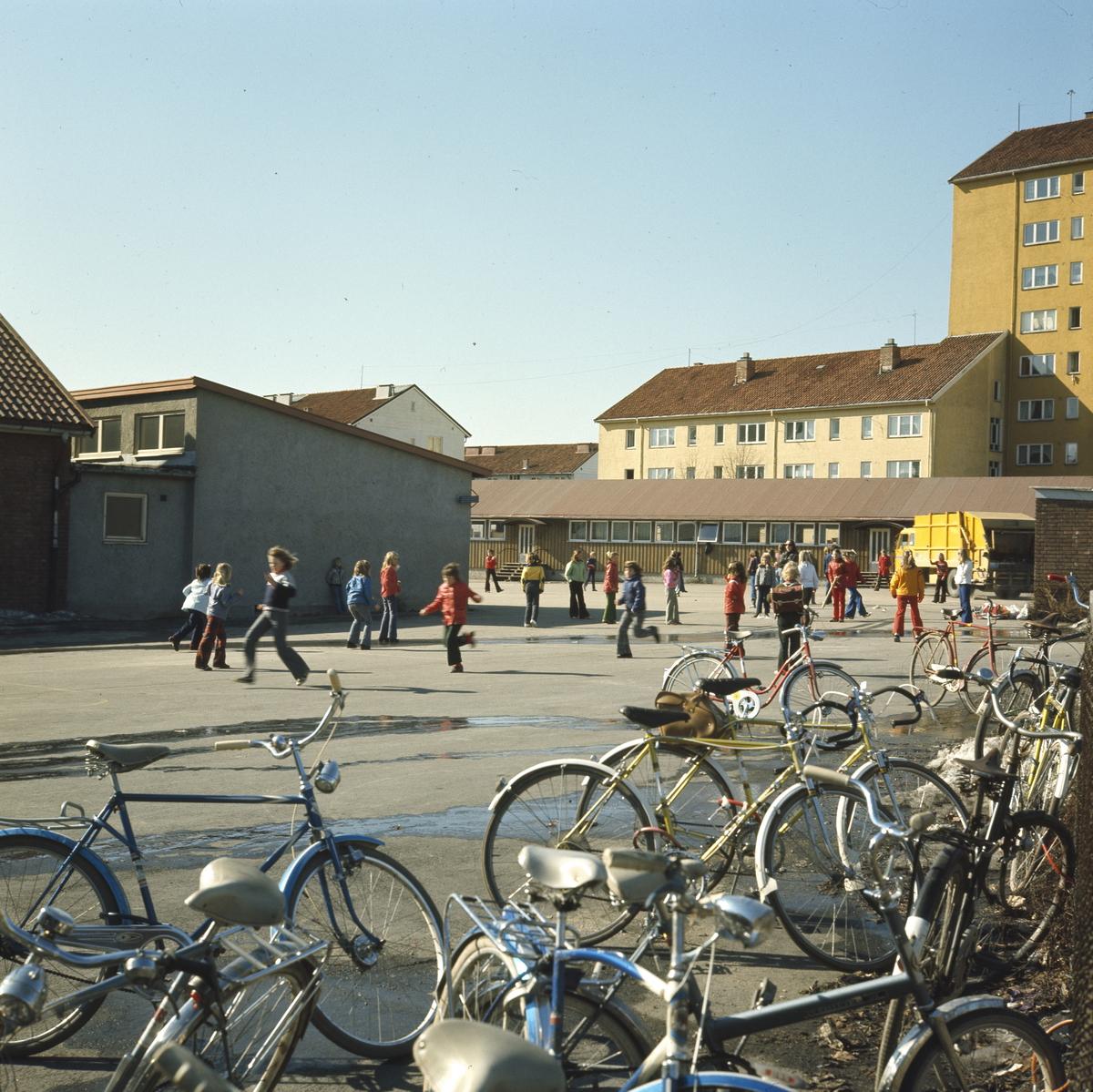 Foto av skoleelever som leker i skolegården ved Årvoll Skole. I forgrunnen en oppsamlingsplass for sykler til elevene.