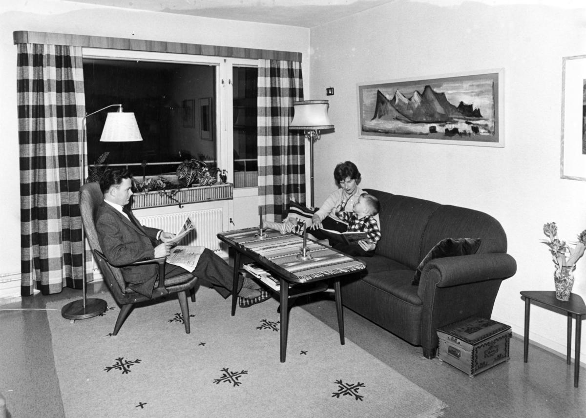Foto av en familie som sitter i ei stue. Far leser avisa mens mor leser for gutten.