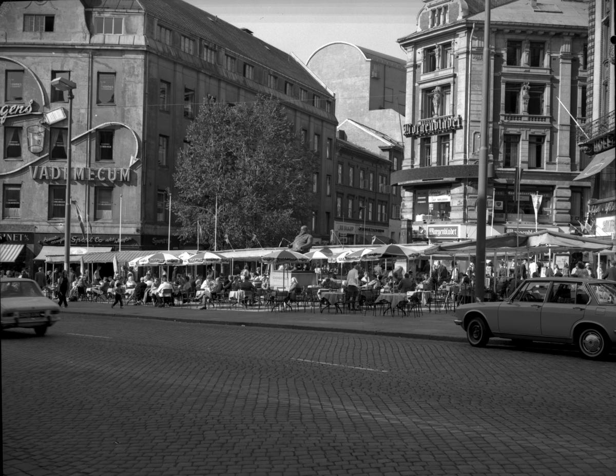 """Uteserveringen som på folkemunne kalles """"Dasslokket"""". Midt på plassen ses statuen av Christian Krohg, utført 1960 i bronse av Asbjørg Borgfeldt og Per Hurum. På husfasaden til venstre ses en stor lysreklame for """"Vademecum""""."""
