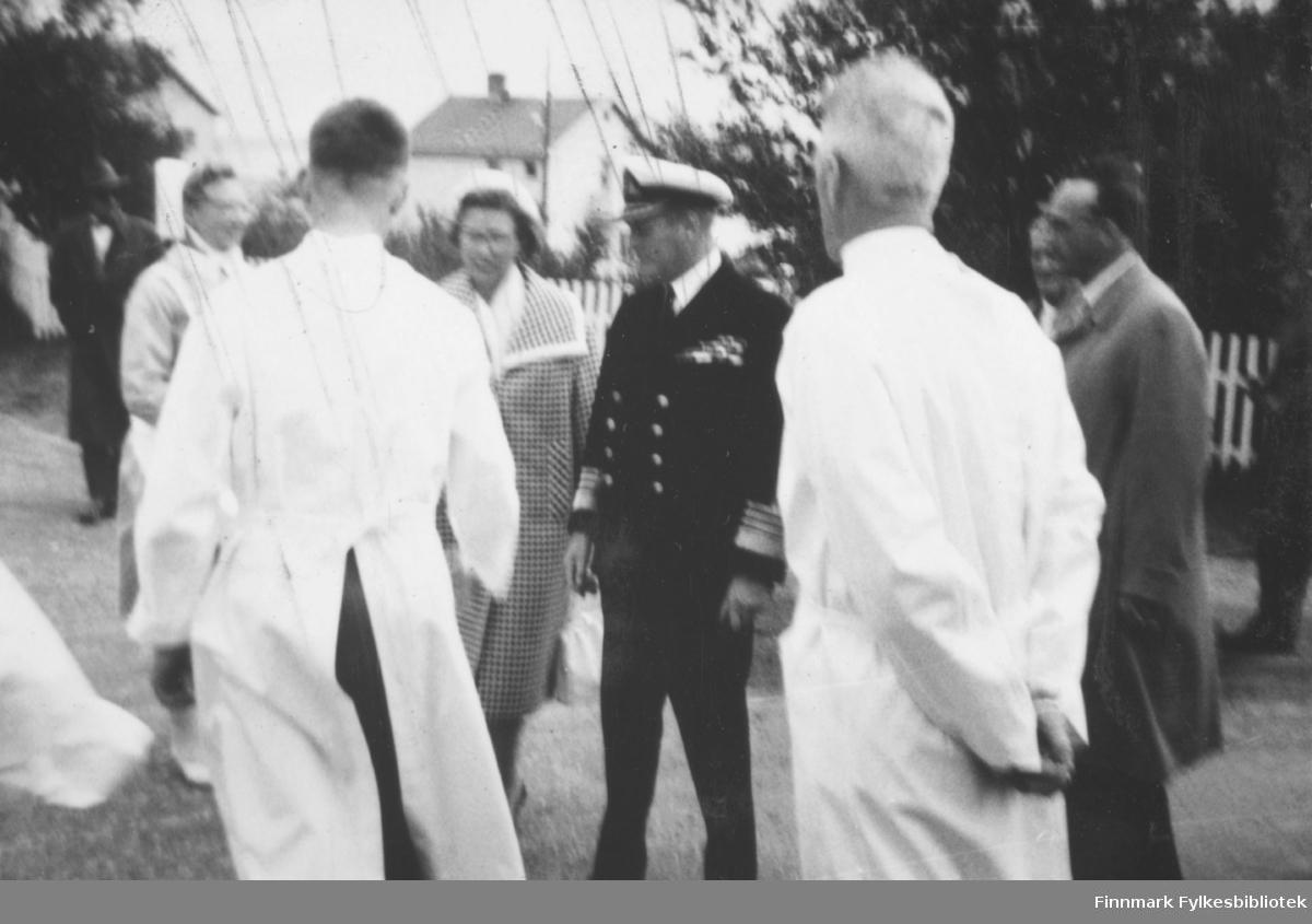 Kong Olav V med følge utenfor Vadsø sykehus. Ved kongens side prinsesse Astrid. Til høyre i bildet ser vi sykehusdirektør Anders Aune, så Bjarne Skogsholm med ryggen til. Bildet er dårlig fokusert