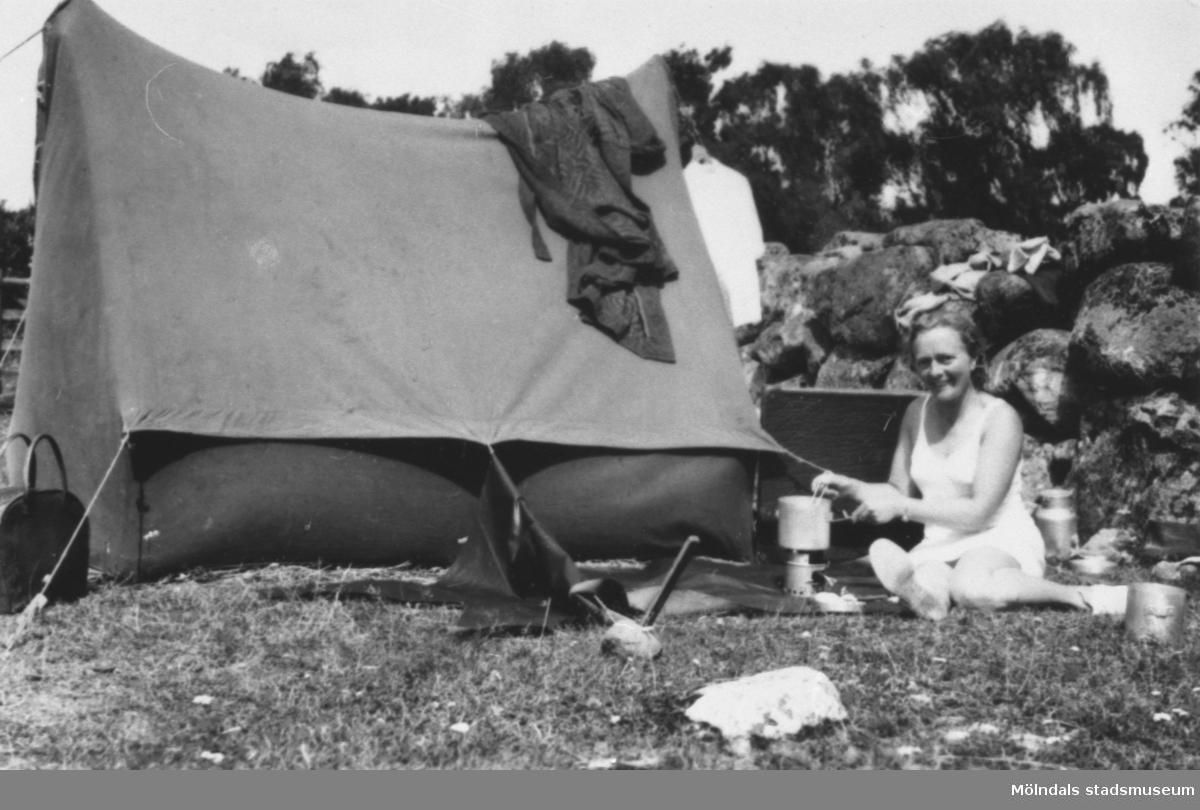 Rosa Pettersson på tältsemester på 1950-talet då familjen hade skaffat en begagnad bil, en Opel Olympia, 1949 års modell. Platsen är någonstans i Blekinge. De reste till olika landskap i Sverige under somrarna. Rosa lagar mat på ett bensinkök.
