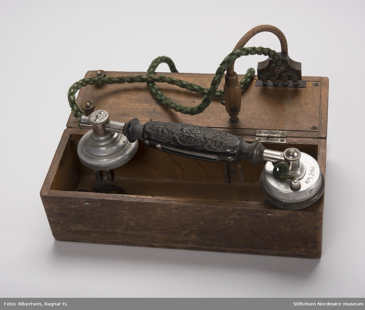 BESKR: Kassen har lærhank på lokket. Innvendig er det to rom. Luren festes til klemmer under lokket. Den plugges fast i et støpsel i en trebunn som ligger over batteriet. En løs ledning plugges fast i kassen og til ledningnettet.  DELER: Kasse, lur, ledning.