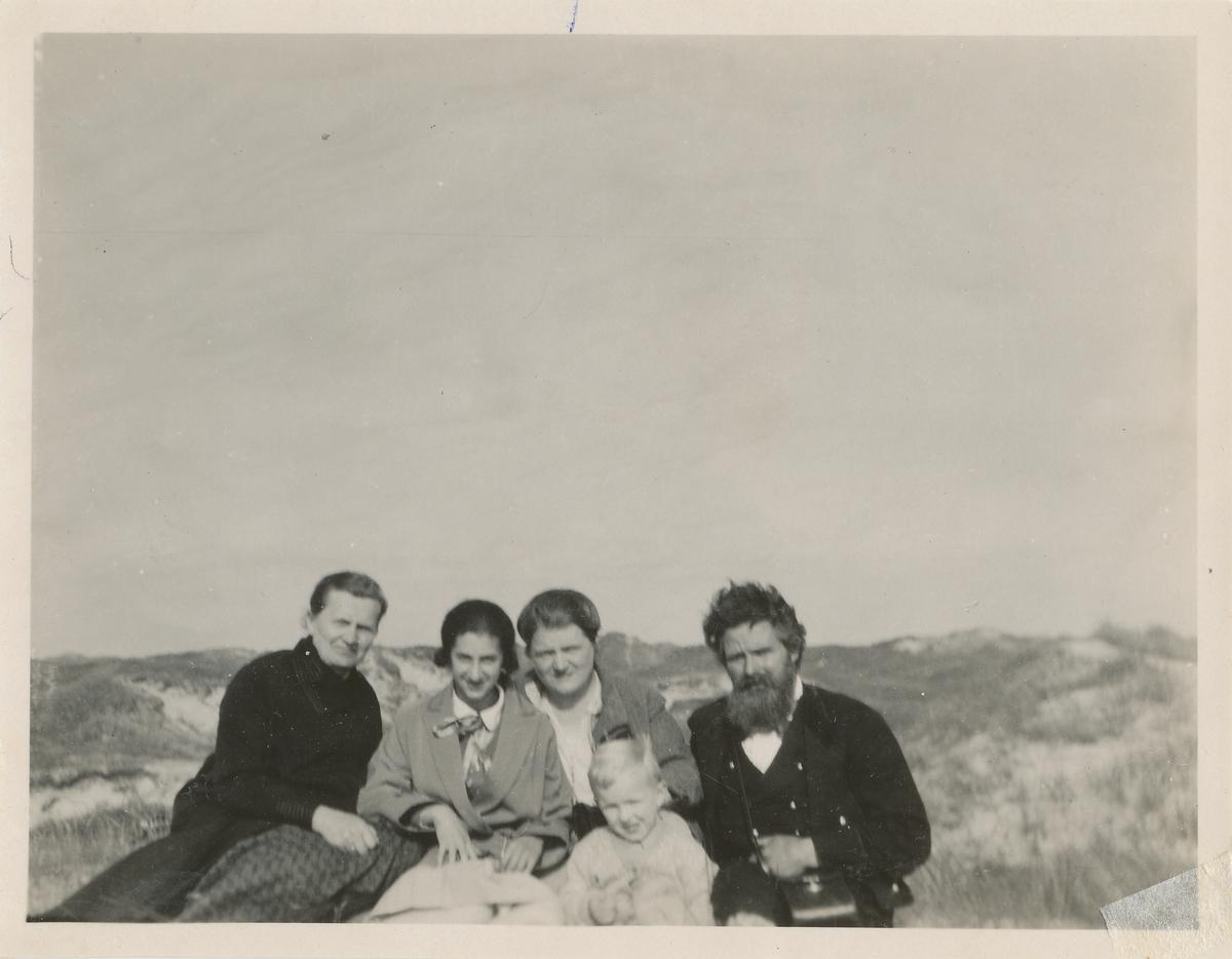 Tre danske kvinner og et barn sammen med Ingvald Skjeldrup i Danmarks gresslagte sanddyner.