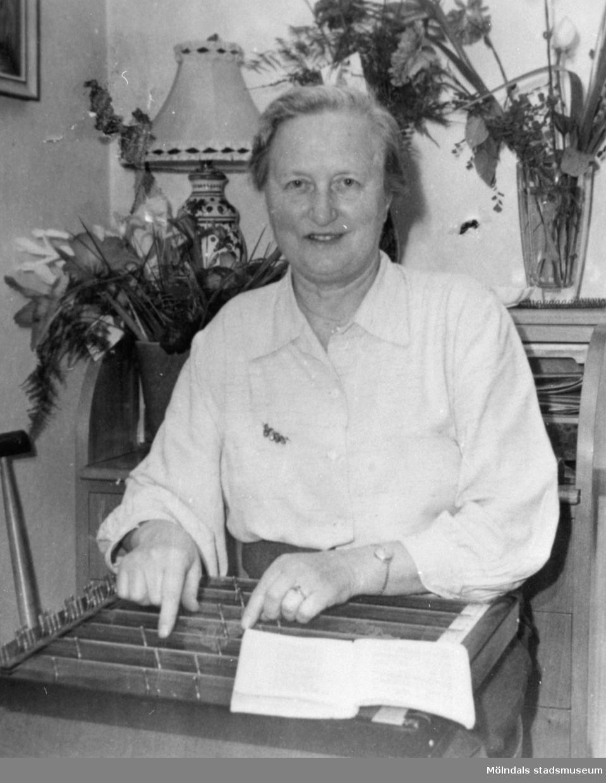 En okänd kvinna som letar i ett register, 1930-tal. Bilden kommer från ett utav Gunnebo slotts album.