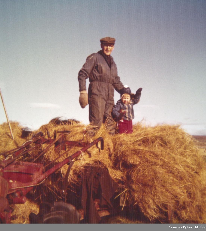 Arnulf og Elin Bauna laster tørrhøy på traktorvogna.