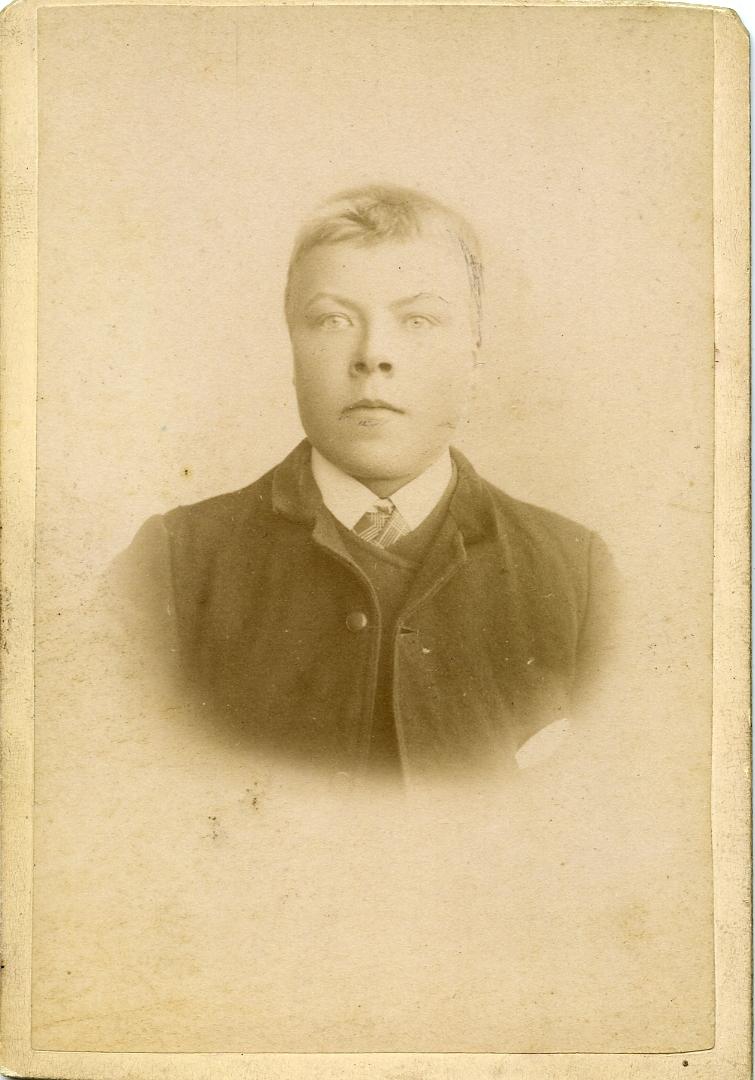 Portrett av yngre mann foran lerret. Mannen er iført skjorte og slips samt jakke.