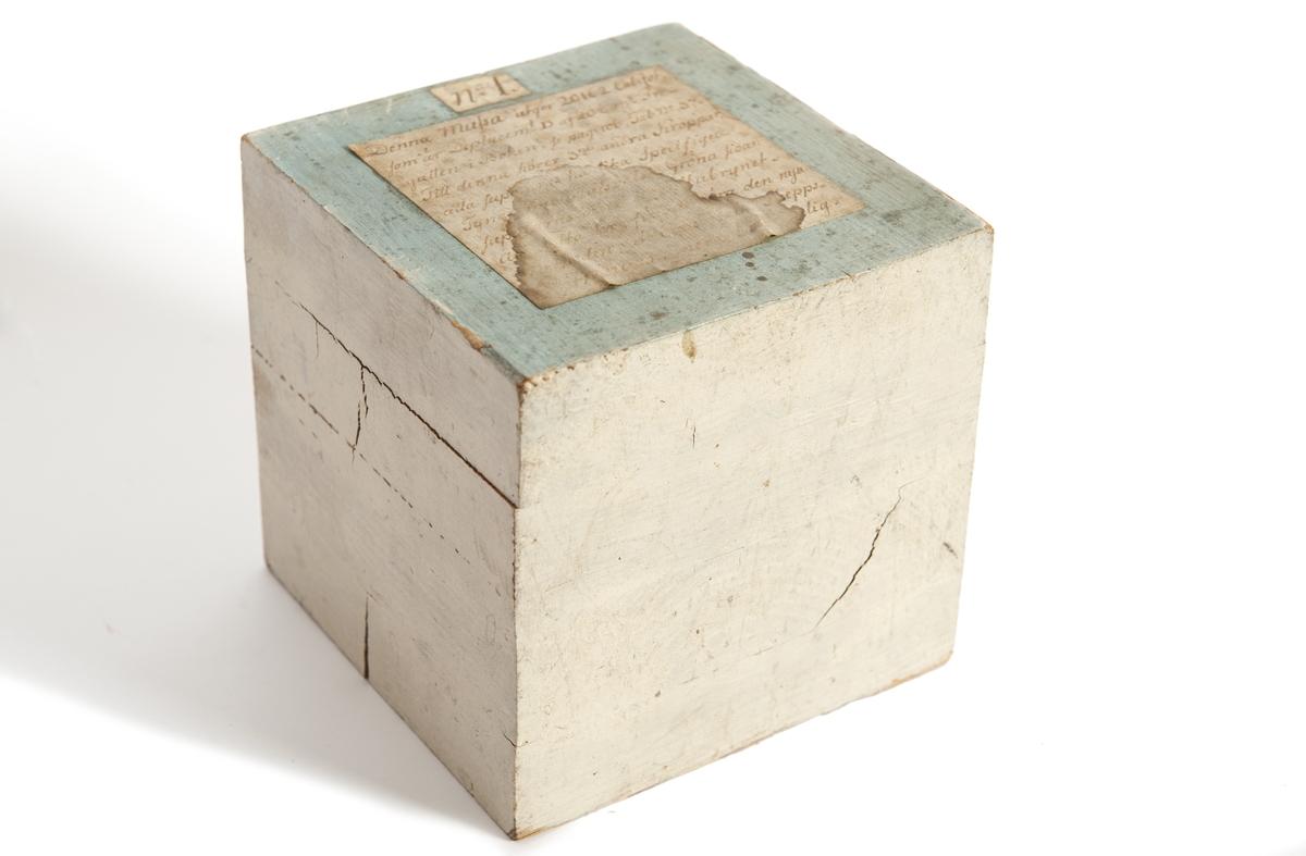 Demonstarationsmodell, kub av trä, gråmålad med grön översida. Märkt å påklistarad lapp ' Kubens kant: 12,5 cm Från modellkammaren i Karlskrona. Från Ingeniörsdep:s ritkontor, Karlskrona 24/10-35
