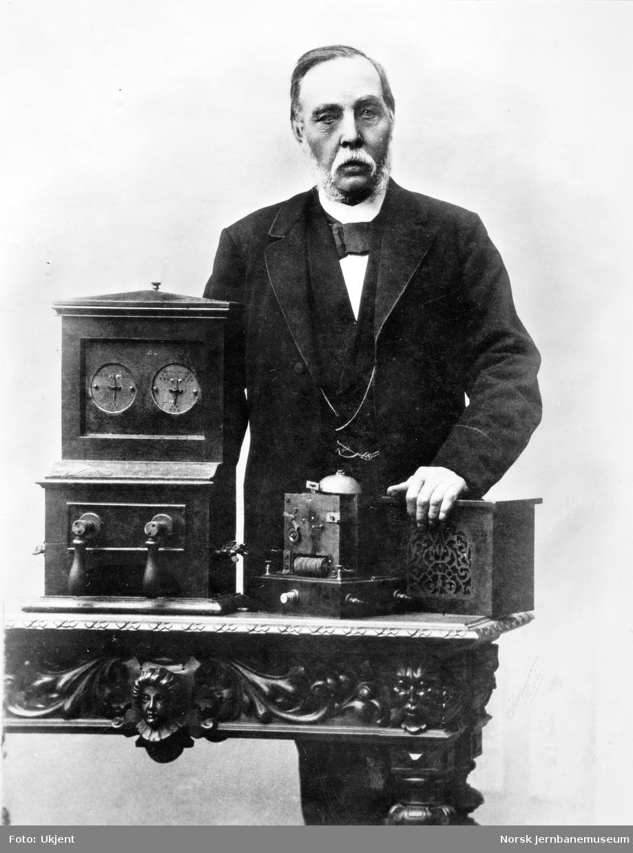 Telegrafinspektør Chr. Wiger med (fra v) Cooke & Wheatstones nåletelegraf, mottakerapparat for signaltelegrafen og en alarmklokke
