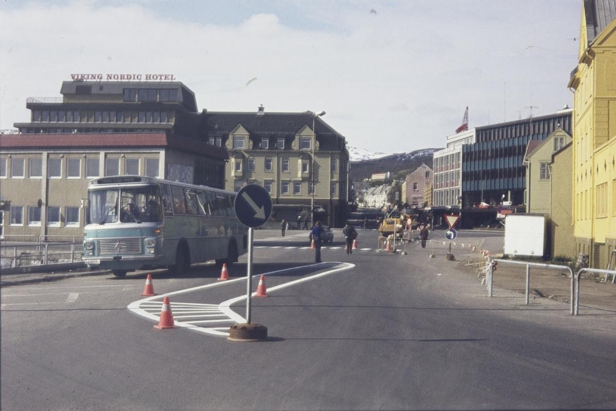 Buss med rutebilstasjonen og Torvet i bakgrunnen.